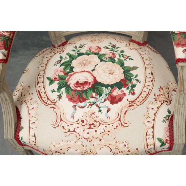 This is a charming pair of Louis XVI style armchairs, painted overall in a putty color and upholstered in a cheery floral...