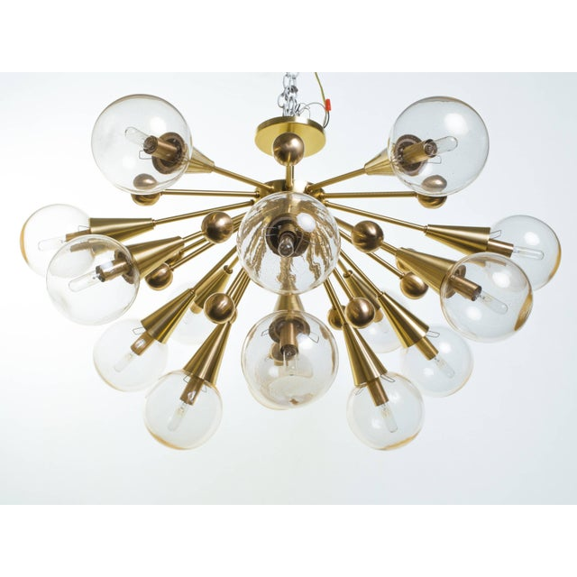 Sputnik chandelier composed of 15 lights and 16 decorative brass spheres produced by Spark Interior. Glass globes with...