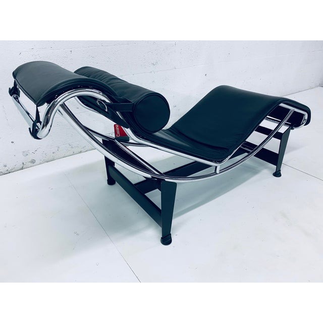 Black leather chaise lounge on tubular chrome and black steel base by Le Corbusier, Pierre Jeanneret and Charlotte...