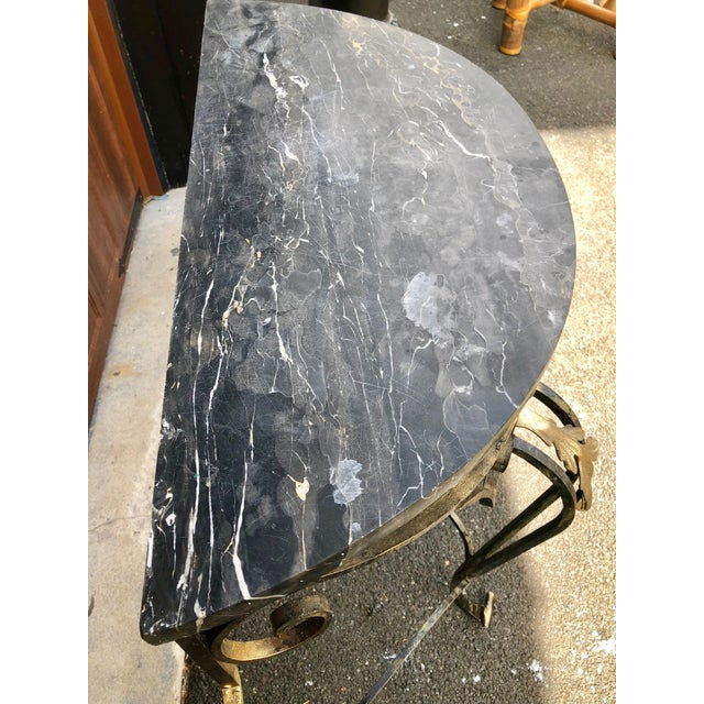 Dramatic Italian wrought iron and black marble console table from the 1950s. Stunning combination of gilt and black floral...