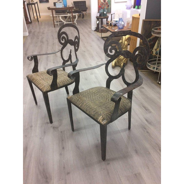 Fabulously sculptural pair of hand-forged iron arm chairs having a wonderful scrolly motif and original rattan seats. One...
