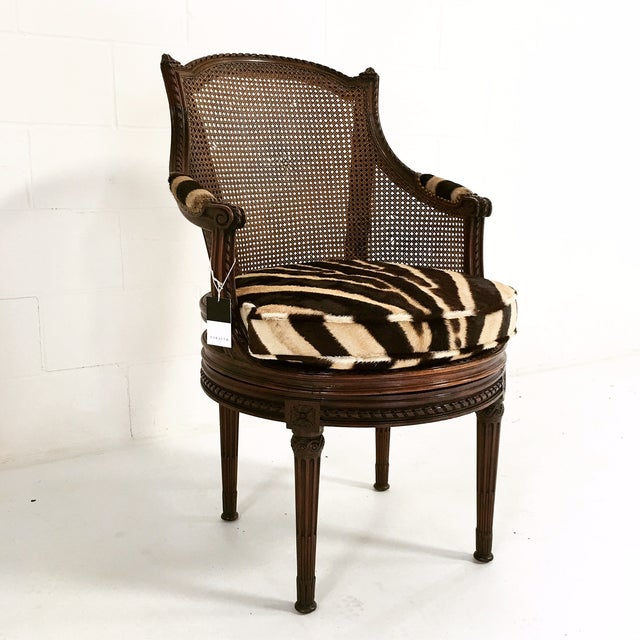 This beautiful, antique mahogany and cane bergere swivel chair is a rare find. We created a custom loose zebra hide...