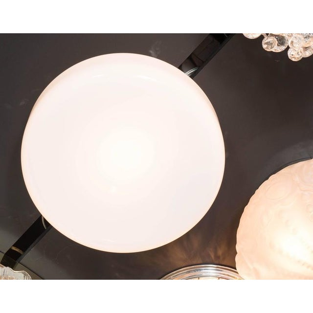 A Mid-Century Modernist flush mount chandelier featuring a seamless circular design in milk glass, when lit the entire...