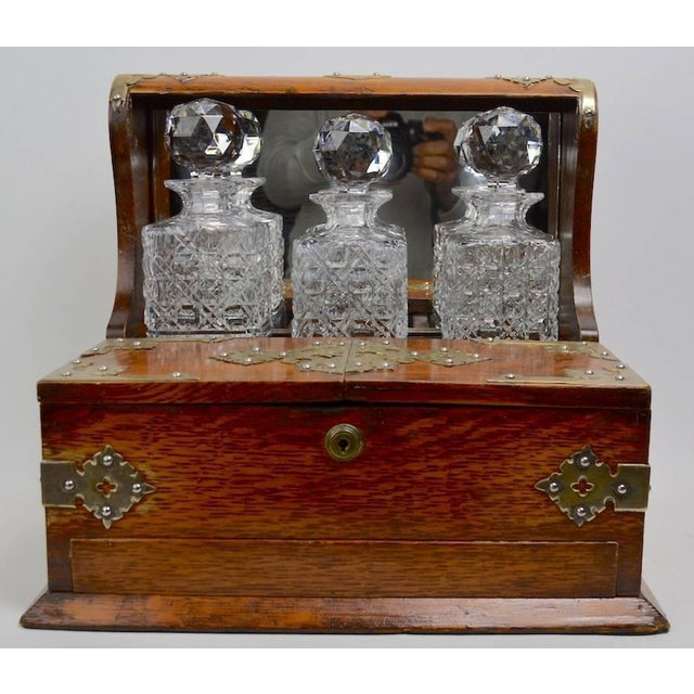 Nice oak case tantalus decanter set by Branah London, with three crystal decanters. The case shows some minor cosmetic...