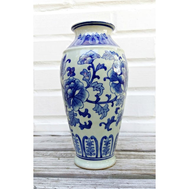 Blue botanical pattern over a background of cream. Urn shape.