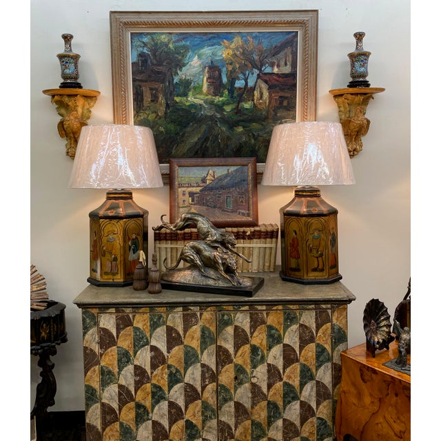 A pair of antique octagonal shaped tole lamps with three asian figures on each and custom shades. Both are numbered, one...