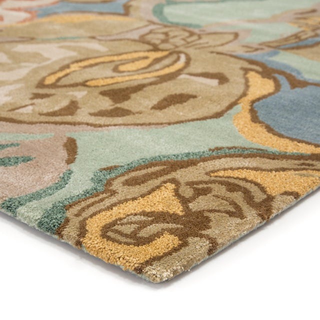 This hand-tufted area rug delivers artistic charm with soft yet playful hues. Watercolor blooms in tan, blue, and red...