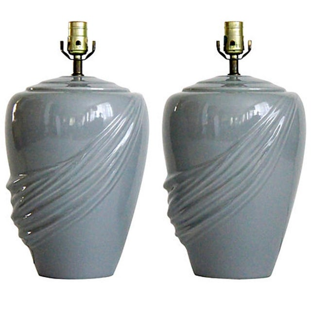 A pair of mid-century gray glazed ceramic lamps in urn-form with draping detail and brass fittings. Original wiring is...
