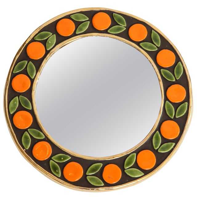 A lovely small, round mirror created by Francois Lembo in France, circa 1960. The frame is decorated in a gold metallic...
