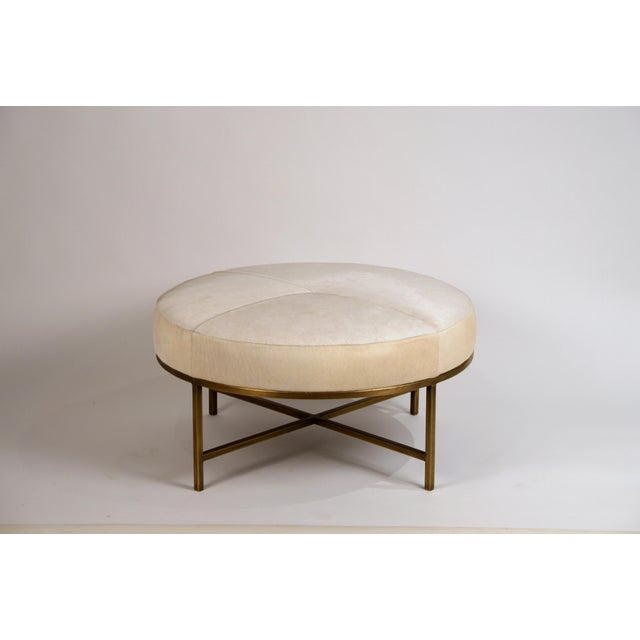 Small white hide and patinated brass 'Tambour' Ottoman by Design Frères. Perfect as a coffee table in the living room, a...