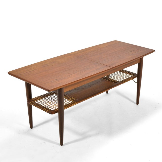 "This exceptional teak coffee table has a top that expands with the addition of a 12"" lacquered teak leaf and conceals a..."