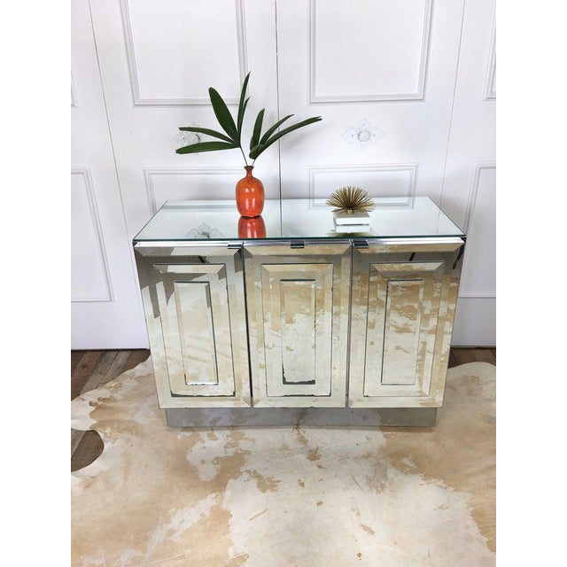 Vintage 1980s mirrored cabinet by Ello. 3 doors with layered mirror. Metal pulls at each door. White laminate interior....