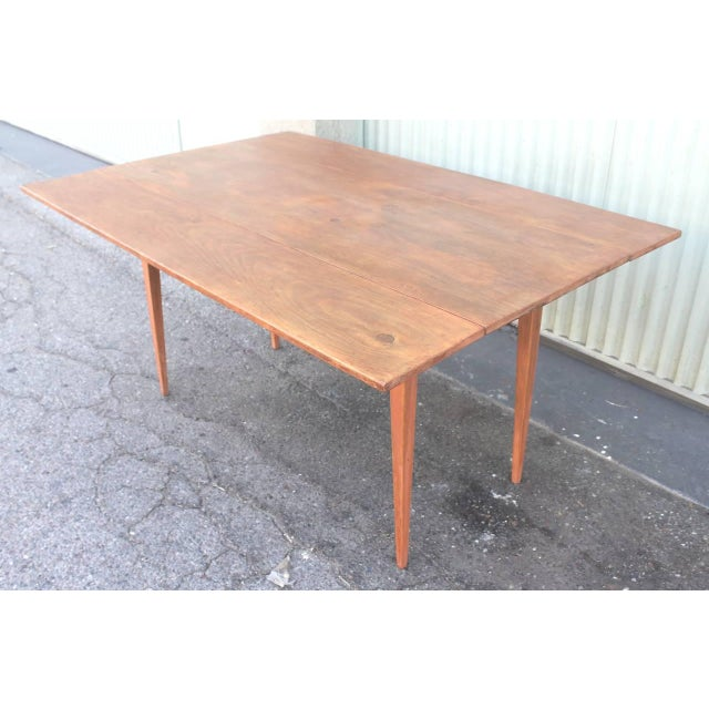 This finely constructed early 19th century pine original salmon painted base with a scrub top farm table also has drop...