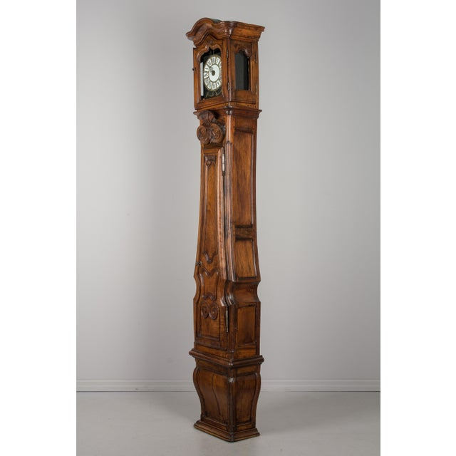 An exceptional 18th century Louis XV style French horloge de parquet, or tall case clock, from Lyon. Made of solid walnut...