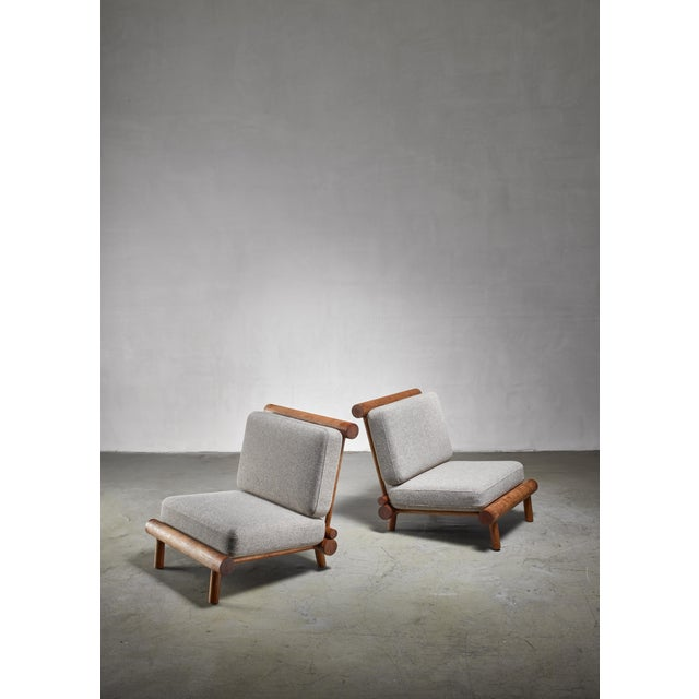 A pair of low, foldable 'chauffeuse' (fireside) lounge chairs in oak, attributed to Charlotte Perriand. The chairs are...