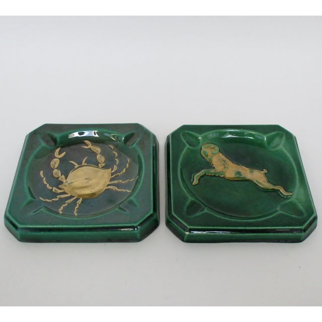 Two vintage ceramic green-glazed ashtrays, each adorned with a gold embossed astrological sign, in the style of Hollywood...