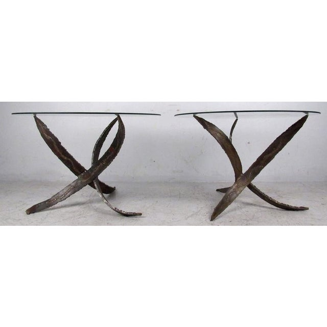 Two vintage-modern end tables each featuring a sculpted metal base and round glass top, designed in the manner of Paul...