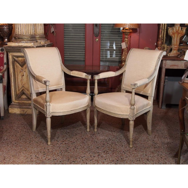 A pair of gray/green painted Directoire style fauteuils, scrolled back, arms on baluster uprights, rosette blocks,...
