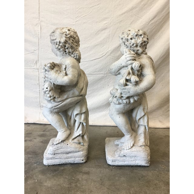 Beautiful pair of Italian antique white patinated cast concrete garden statues, two putti (angel) scantily clad in floral...