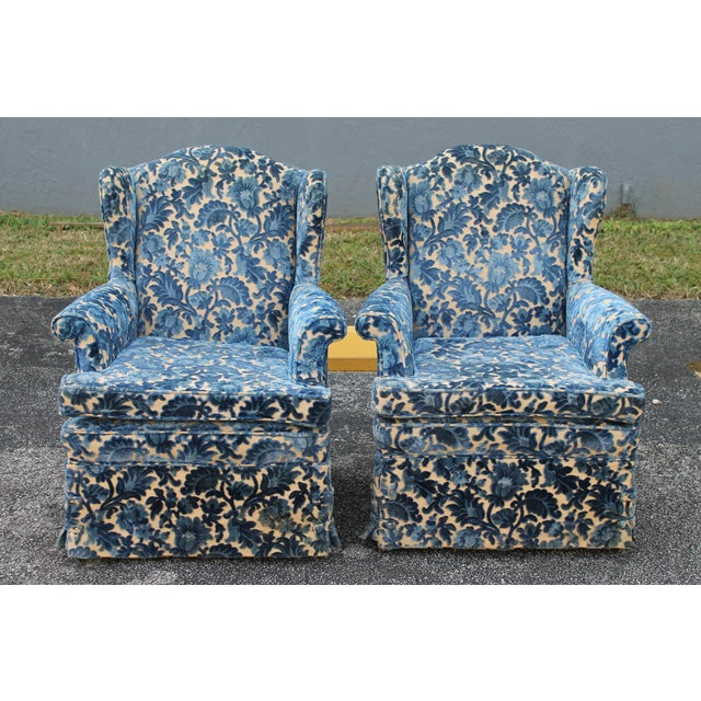 A pair of heavy textile cut velvet 1970's Wingback Chairs. Beautiful blue on a muslin background. Buttoned skirt on...
