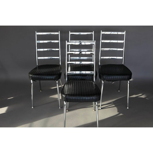 Set of four chrome-backed dining side chairs with black vinyl upholstery. No rips in the vinyl, sturdy construction.