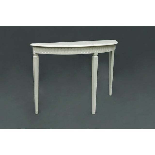 This semi-circle console table has 3 tapered legs, and is finished in an antique white matte finish. The apron is...