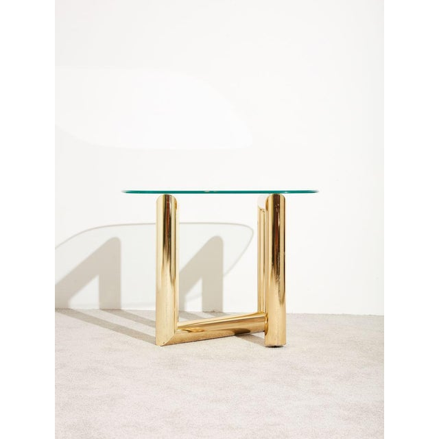 Circa 1970s glass and brass side table. The glass top is cut in a rounded rectangular form with polished ogee edge. The...
