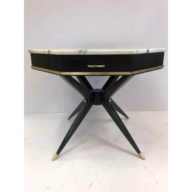 1950s, Italian marble top, center table with an octagonal shape. Ebonized base with brass trim, sabots and accents. Table...