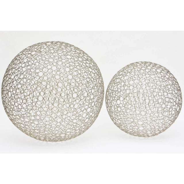 These two different size diameter sculptural floor balls have intricate pattern of side by side circles of 4 different...