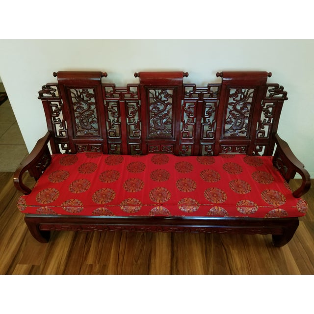 Absolutely stunning carved rosewood settee with intricate detail. In very good vintage condition. The cushion is also in...