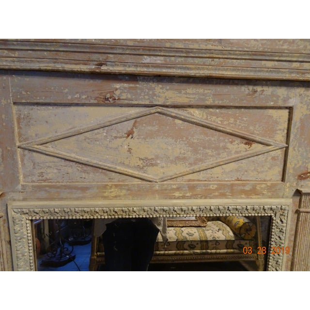 Very rustic in the painting this mirror is 19th Century, French Directoire style. The wood carving around the mirror is...