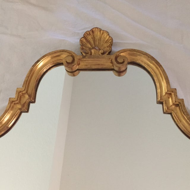 Striking gilded Vintaged gold mirror in solid wood frame with shell measures 43.25 x 24.25 x 1.5. Shell measures 4.5 x 4...