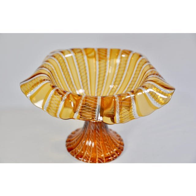 Wonderful craftsmanship is captured in this glass footed candy dish from Murano, Italy. The ruffled rim, knurled piece...