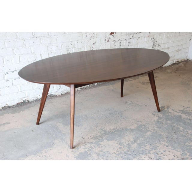 Offering a very nice dark walnut Elliptical dining table or conference table by Knoll. The table has nice tapered legs and...