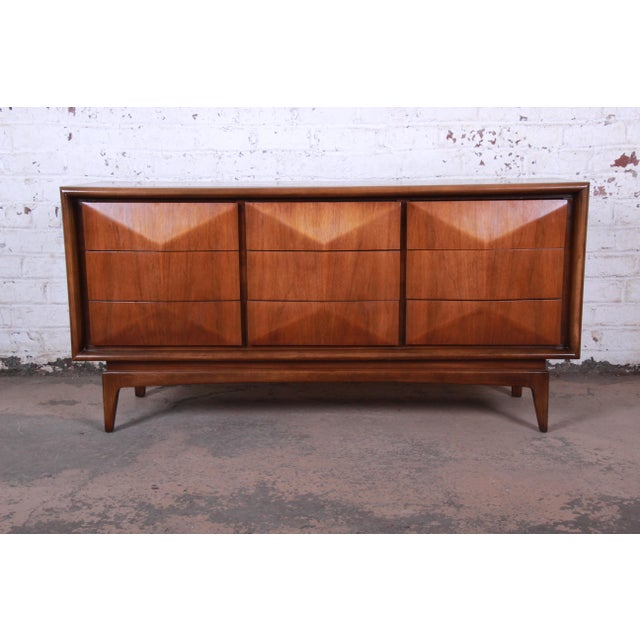 A unique and exceptional mid-century modern sculpted walnut triple dresser or credenza by United Furniture. The dresser...