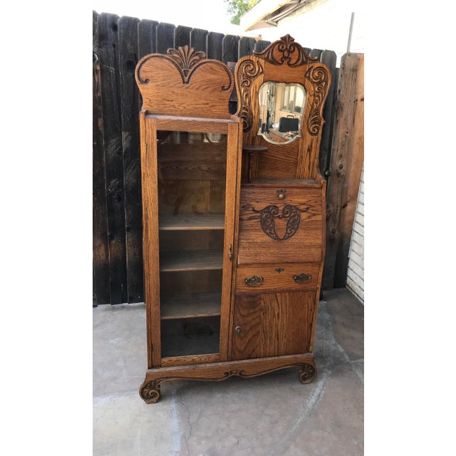 This is an antique tiger oak glass secretary writing desk. Side by side piece has a beautiful carved silhouette on the...