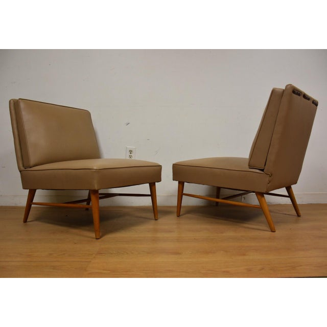 A rare pair of mid century modern slipper lounge chairs in beige vinyl with a slight grey undertone. The tapered maple...