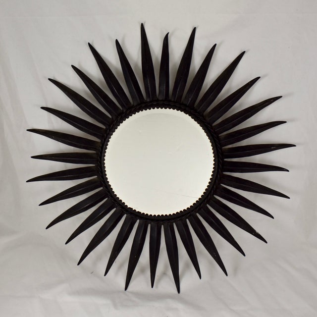 A large, heavy, Mid-Century French, black finished wrought iron Sunburst wall mirror. Tapered, convex shaped sun rays...
