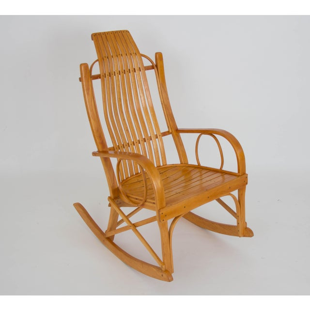 A handcrafted rocking chair in the style of Amish bentwood pieces. This example is made of oak slats laid close together...