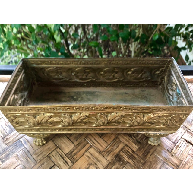 A fantastic brass repousse planter. It has a scrolling ivy motif that wraps completely around and sits perched upon four...