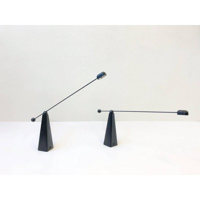 An amazing pair of 1980s black lacquered adjustable table lamps by Ron Rezek. The lamps are in amazing condition. They...
