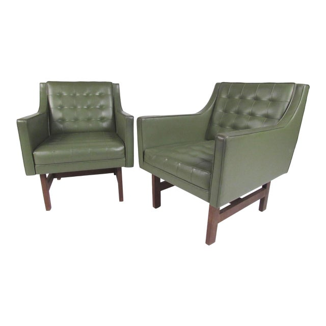This pair of vintage vinyl club chairs feature stylish sloped armrests, tufted seat backs, and teak frames. Mid-Century...