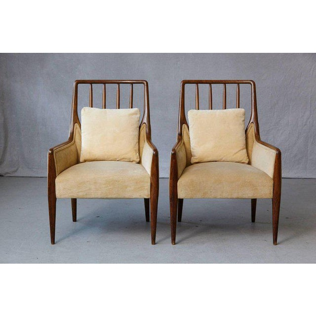 Exceptional pair of high back walnut lounge chairs in gold beige velvet fabric with matching pillows in original...