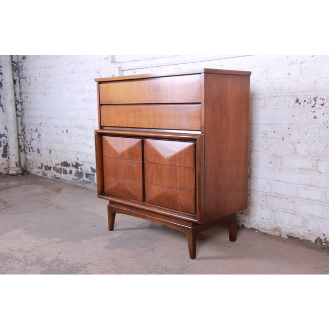 An exceptional mid-century modern diamond front highboy dresser by United Furniture Co. The dresser features beautiful...