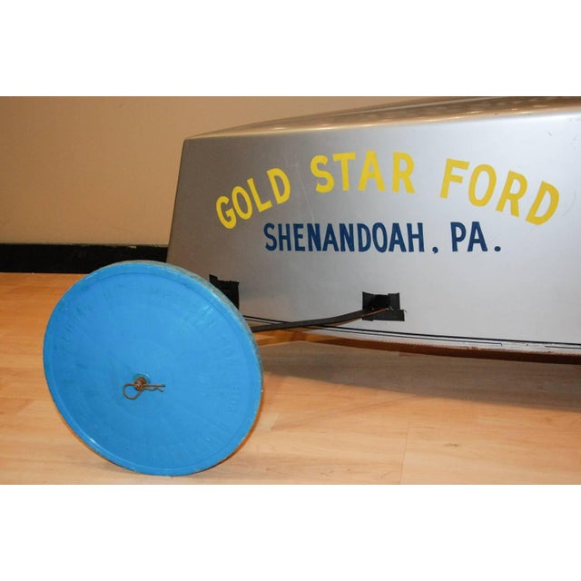 Circa 1980 A sleek metallic silver soap box derby car from Shenandoah, Pennsylvania driven by Buzzy Burns. The car has...
