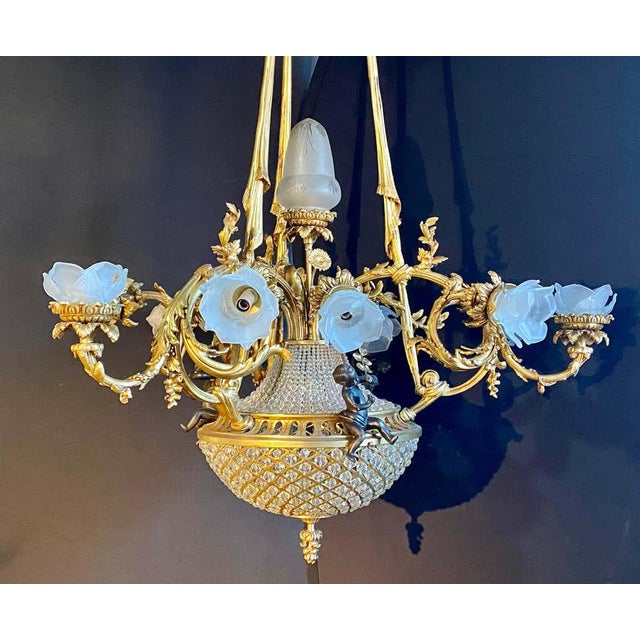 Pair of crystal beaded globe dore and patinated bronze cherub form 15-light. The cherubs measure 6.5 inches in height....