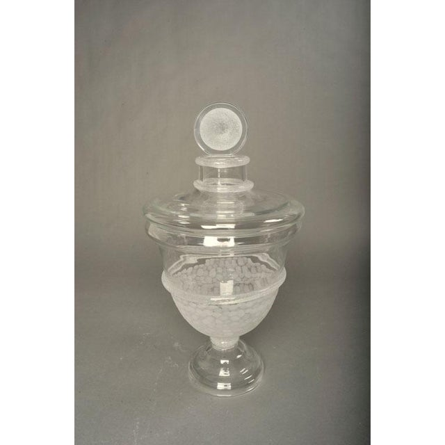 An exquisite large apothecary jar with a substantial lid, an urn-shaped body and a footed base; the whole in clear glass...