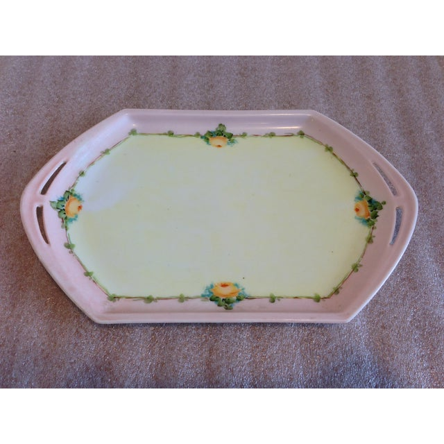Antique hand-painted small porcelain tray showing a floral border of tiny green leaves and orange roses, pale pink and...