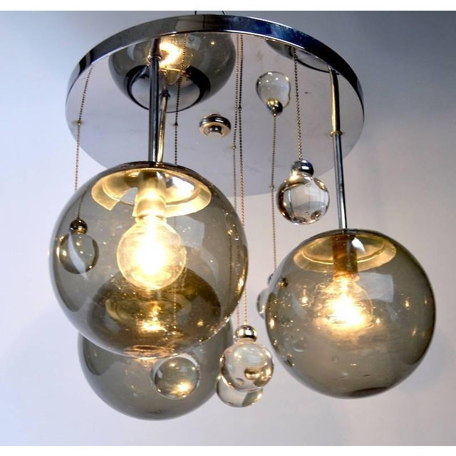 Stylish chrome and glass ball drop chandelier. The circular chrome disk mounts to the ceiling crystal balls hang from...