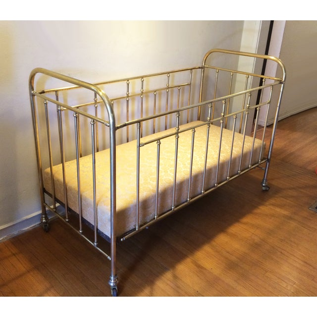 Beautiful and rare antique solid brass baby crib from the late 1920's. Original spring mattress with newer fabric. It has...